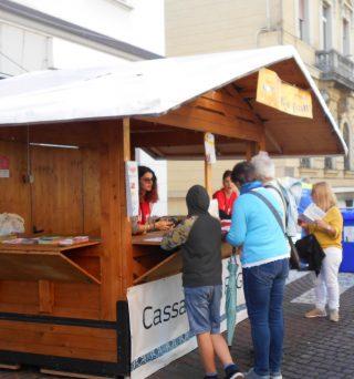 In questa immagine si può vedere una delle casette di legno adibita ad info-point con una collaboratrice che da indicazioni ad un gruppo di avventori.